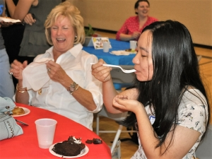 Joanne Dong, an international student from China, enjoys a typical American dessert at the International Welcome Party on Aug. 28. On her left, her sponsor, Vicki Thomason, enjoys the festivities.
