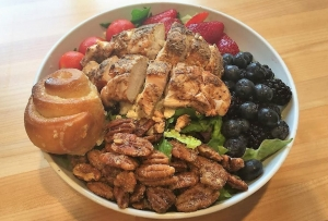 Urban Cookhouse's Berry Good salad features seasonal berries, tomatoes, spiced pecans, feta, and the restaurant's signature vinaigrette, along with a choice of optional proteins such as chicken salad, lime-marinated steak, and grilled chicken.