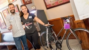 Eric Courchesne, executive director of the Sassafras Center, celebrates with Princess Nash of the Druid City Dames who won a Queen City Cycles, Inc. bike at the Sassafras Beer Festival.