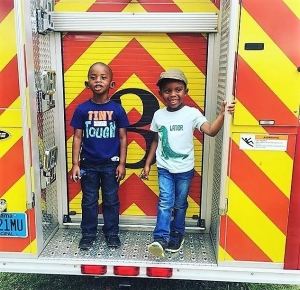 Beaux William and his friend DJ Brown hanging out on a Tuscaloosa Fire Department truck during a summer community awareness event. When it comes to costume shopping for your children, community helper costumes are a great way to go.