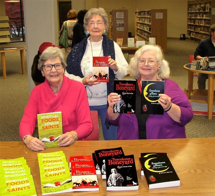 L-R: Patt Devitt (Spiritual Foods for Senior Saints), Aileen Henderson (The Horses of Lost Valley), and Carolyn Ezell (pen name Carolyn Breckinridge) (Tuscaloosa Boneyard) with their books at the Tuscaloosa Public Library Open House event on Dec. 4.