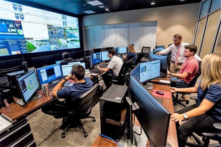 Workers monitor and study traffic in the Traffic Management Center (TMC) of the University of Alabama's Center for Advanced Public Safety (CAPS) office.