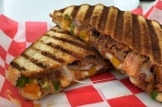 "With muenster cheese, chipotle sauce, pork BBQ, onion, bell pepper, and jalapenos, this sandwich, ""The Gentleman,"" is a staff favorite."