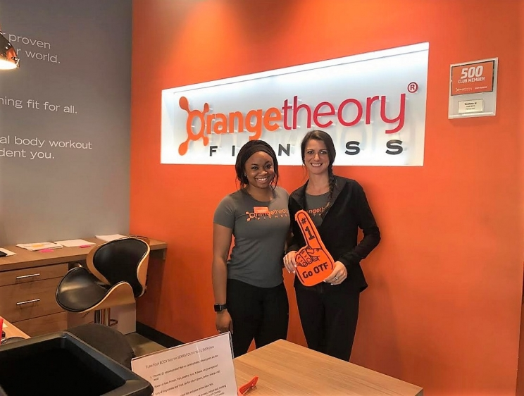 Sales associate Marisha Smith (left) and studio manager Samantha Shannon are all smiles, welcoming new clients to Orangetheory Fitness every day.