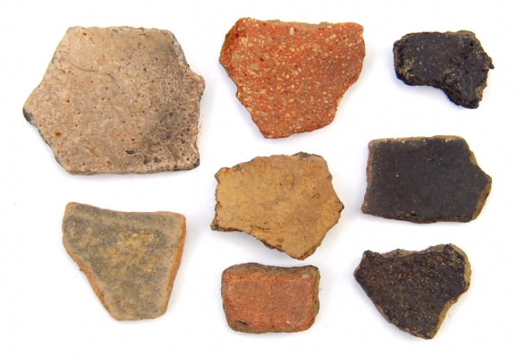 Woodland and Mississippian stage pottery sherds from about 2000 to 500 years ago, all found in Tuscaloosa. Carbon deposits on the three on the right are likely from cooking. The white speckles on the top middle sherd are mussel shell fragments added as a tempering agent to help prevent cracking during firing.