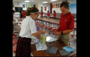 Madelyn Butson and Cooper Davis follow the steps to make ice cream in science class.