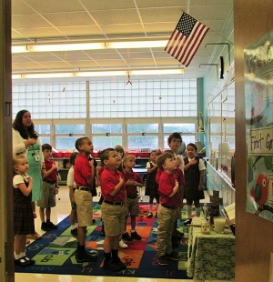 Jenna Strickland's first grade class recites the Pledge of Allegiance. Students and teachers of Holy Spirit Catholic School started the new school year on Thursday, August 6.