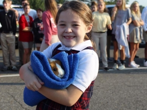 Ella Townsend holds a guinea pig at the pet blessing held at Holy Spirit on Oct. 4.